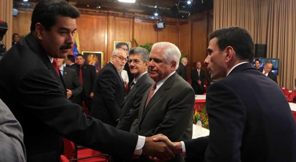 El presidente Nicolás Maduro y su opositor Henrique Capriles se saludan de apretón de mano.e comenzar la reunión